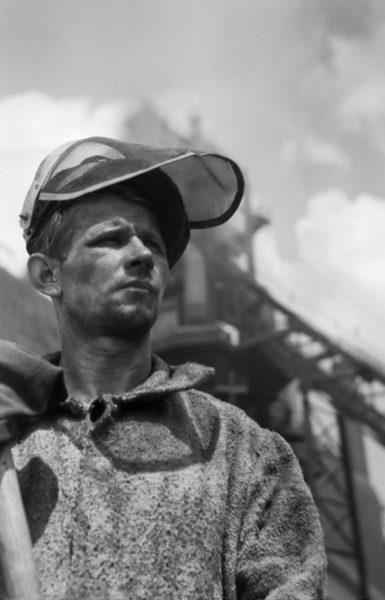 Hutnik przed halą Wielkiego Pieca pozuje oparty na łopacie, z podniesionym kaskiem.