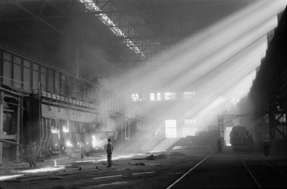 Postać robotnika na środku wielkiej hali fabrycznej, z umieszczonych u góry okienek wpadają strumienie światła.