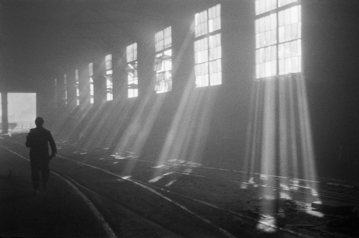 Postać w kombinezonie roboczym przemierza pustą halę fabryczną, do ciemnej przestrzeni wpadają promienie słońca dzielone rytmem pionowych szprosów.