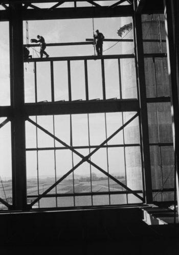 Postaci trzech robotników montują ażurową konstrukcję hali fabrycznej, za nią widoczny pagórkowaty krajobraz.