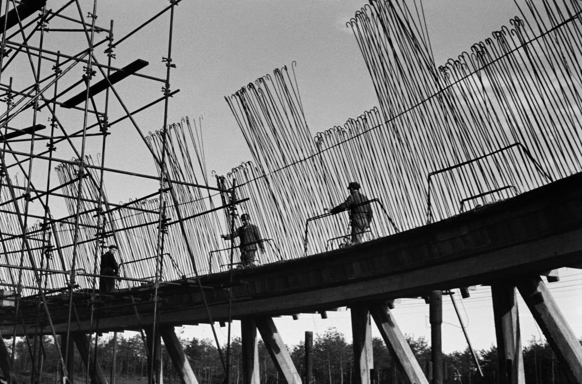 Robotnicy montują pionowe zbrojenia chłodni kominowej.