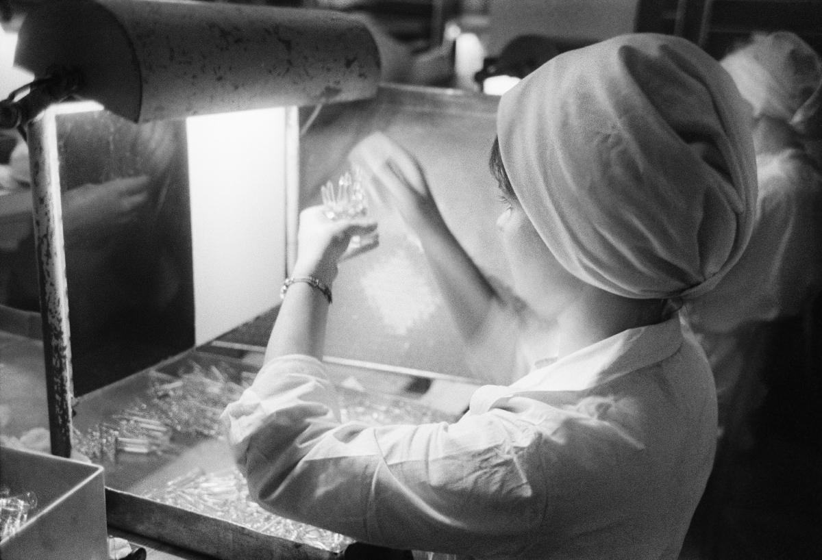 Laborantka sprawdza pod światło zawartość szklanych fiolek