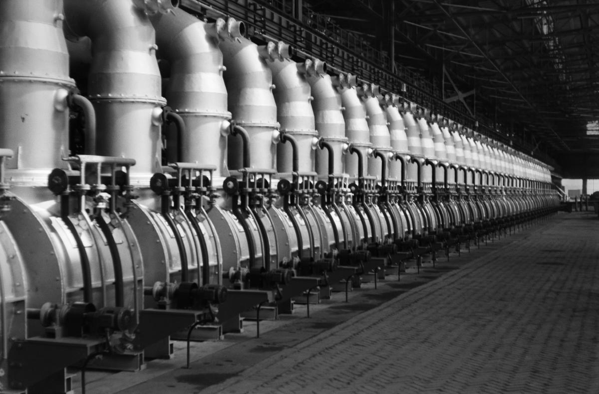 Pogrążoną w półmroku fabryczną halę wypełnia po jej kres instalacja umieszczonych szeregowo poteżnych konstrukcji rurowych.