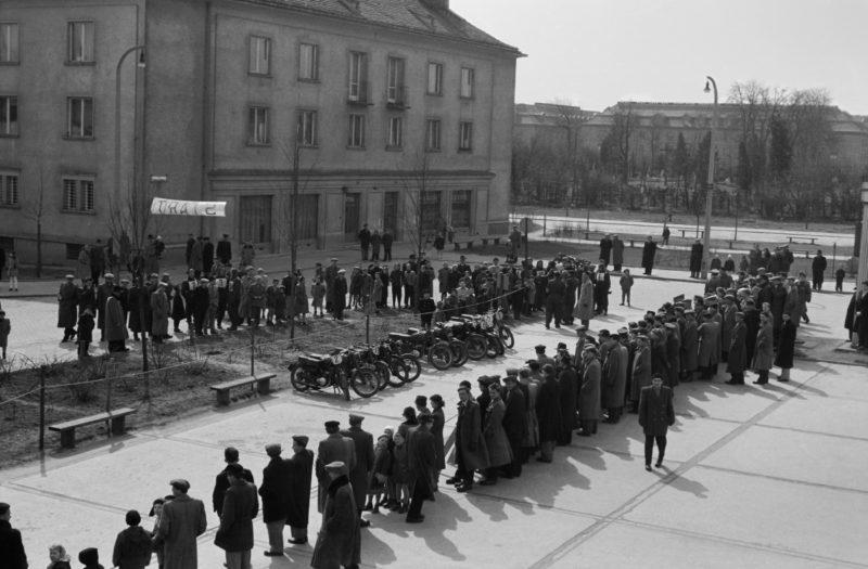 Grupa osób na placu miejskim, w kombinezonach motocyklowych, zgromadzona w przeciwległych szeregach wokół motoyckli.