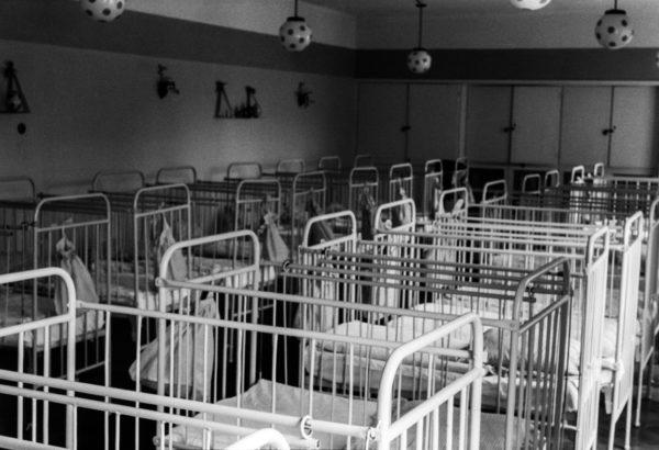 Wnętrze pogrążonego w półmroku żłobka wypełniają rzędy pustych, metalowych łóżek. Nad co drugim łóżkiem zwisa lampa imitująca piłkę nożną.