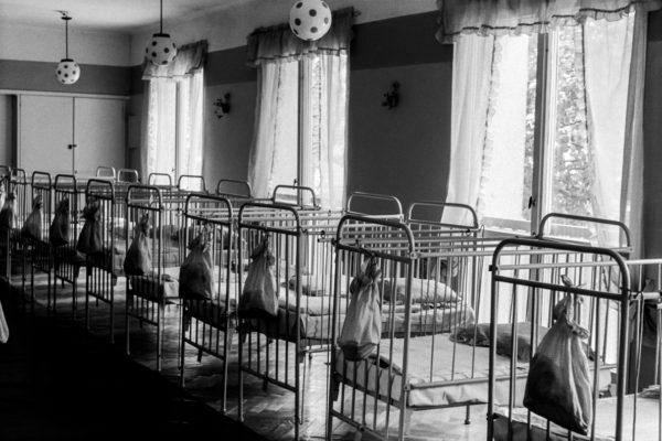 Ujęcie trois cadres przedstawia szereg zaścielonych, metalowych łóżek. Okna skrywając firanki.