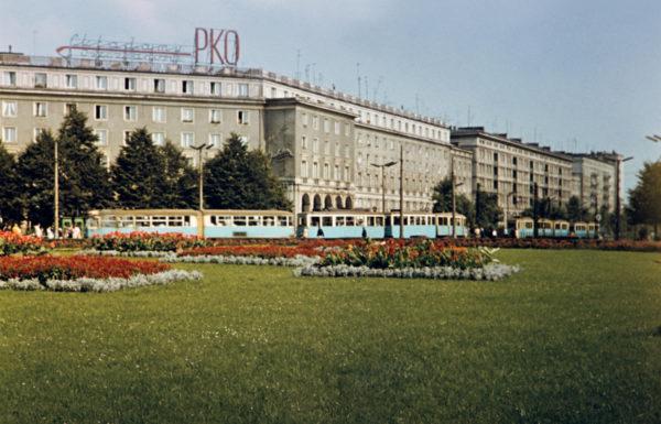 """Kolorowa fotografia w konwencji pocztówkowej przedstawia pokryty przystrzyżonym trawnikiem plac miejski, klomby z kwiatami, na drugim planie przejeżdża błękitny tramwaj, w tle socrealistyczna zabudowa zwieńczona neonem """"Składamy oszczędności w PKO"""""""