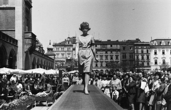 Rynek Główny w Krakowie. Czarno-biała fotografia przedstawia modelkę na otoczonym przez tłum podeście.
