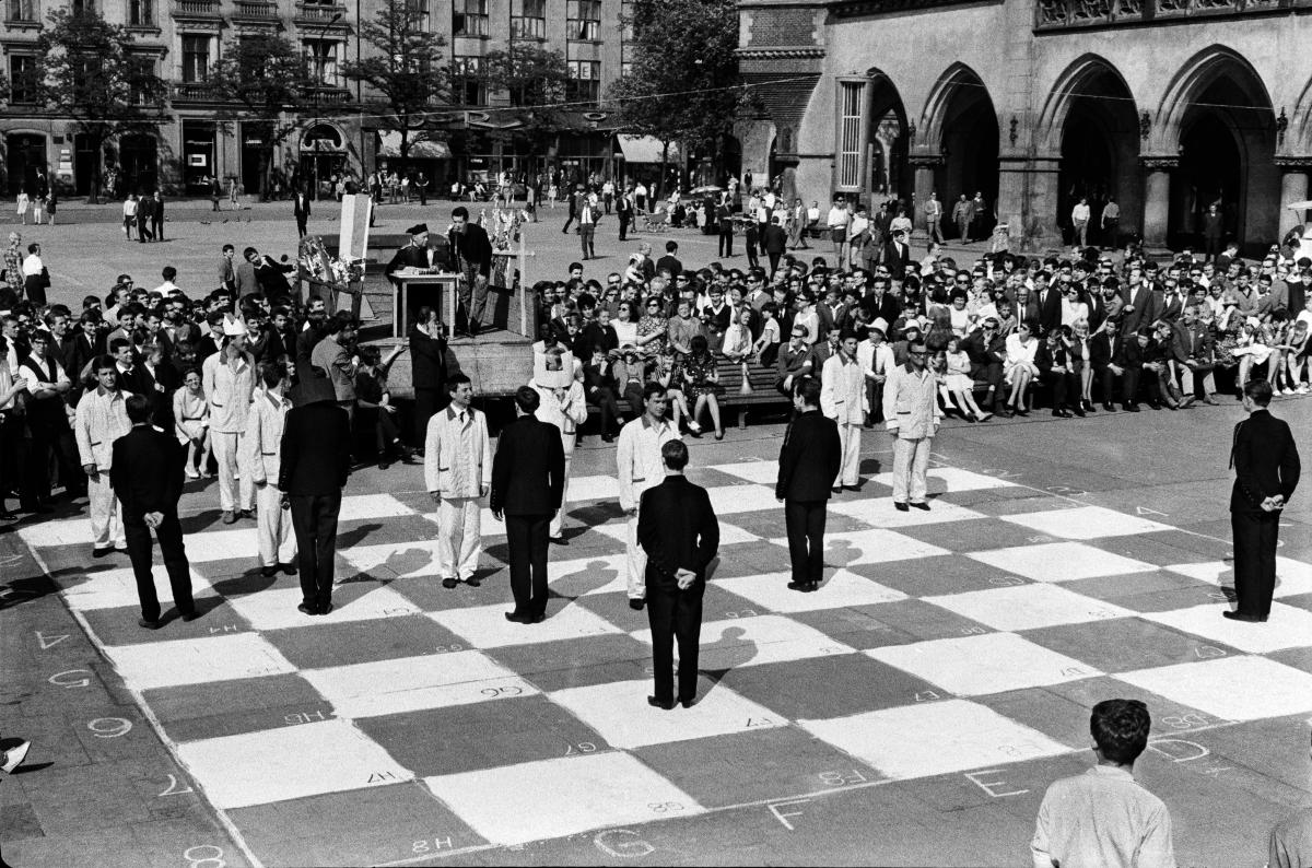 Ubrane w czarne i białe uniformy postaci ludzkie zajmują miejsca na szachownicy namalowanej na płycie Rynku Głównego w Krakowie.