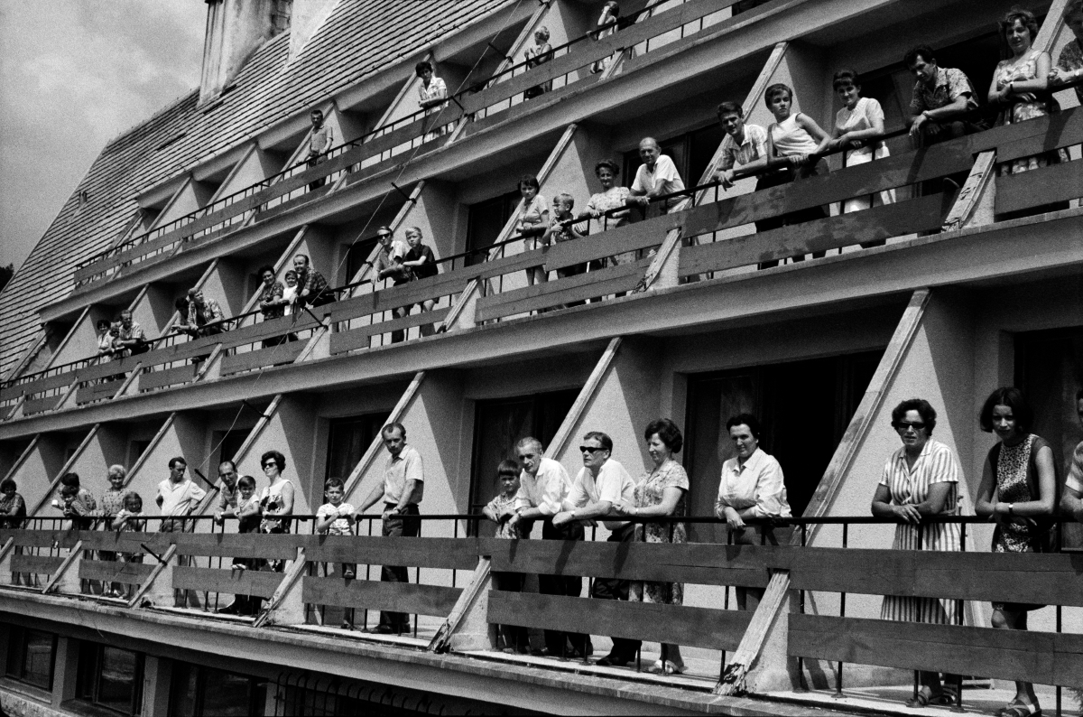 Ludzie na balkonach ośrodku wypoczynkowego pozują do zbiorowego zdjęcia