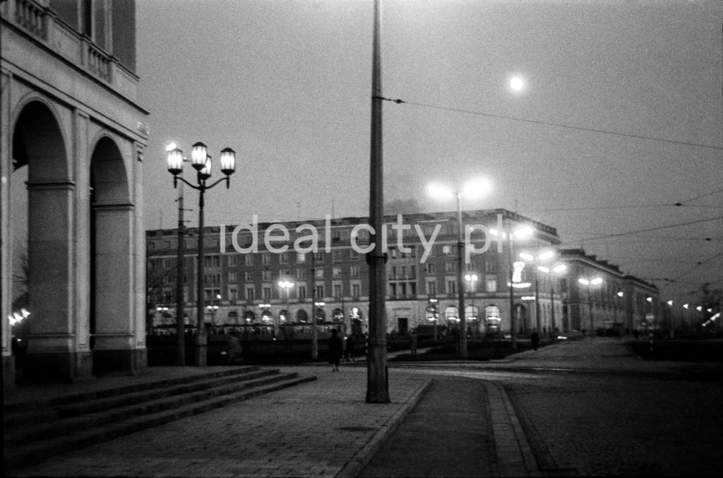 Ujęcie na perspektywę placu i okalających go budynków wraz z latarniami.