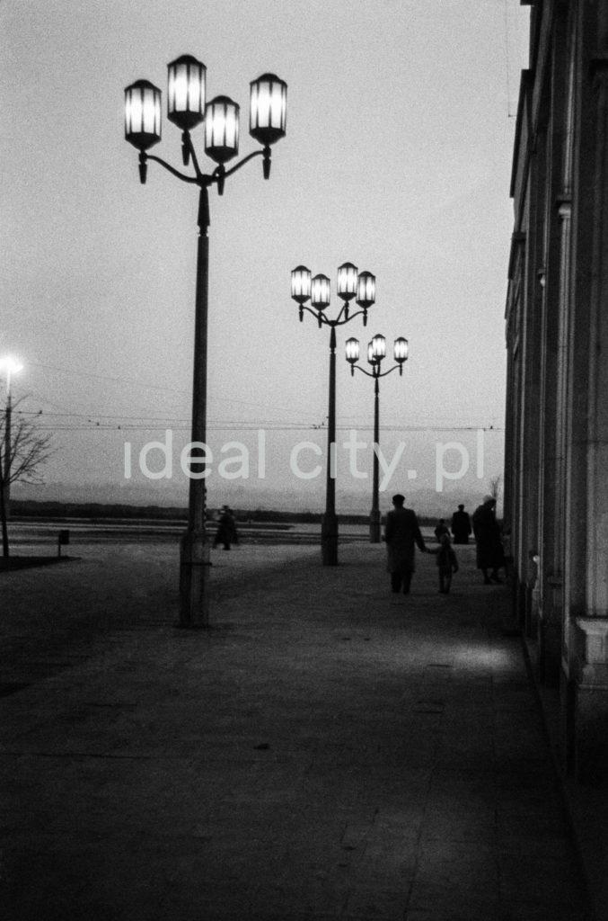 Pionowe ujęcie na szereg rozświetlonych latarni ulicznych w stylu socrealistycznym, na chodniku sylwetki ludzi.