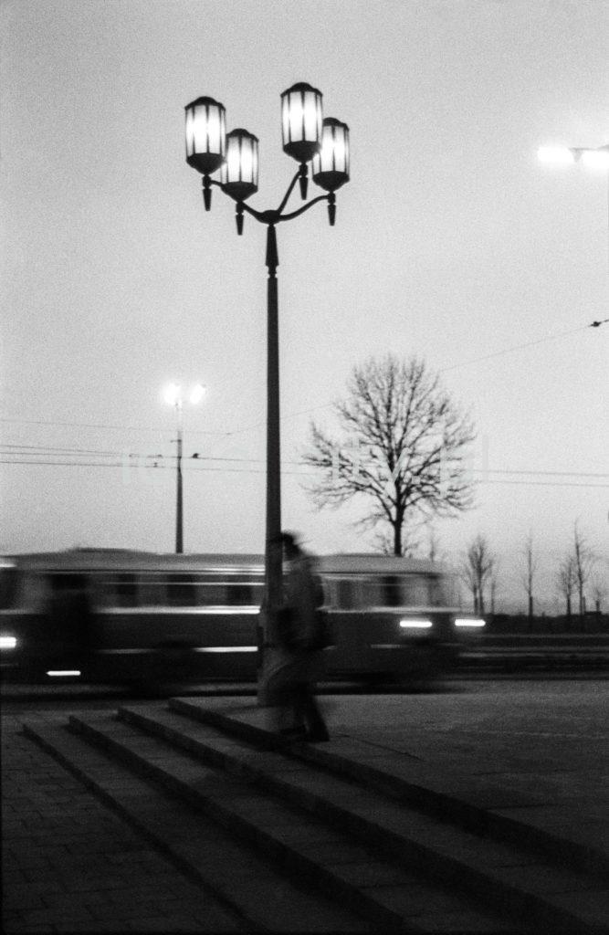 Pionowe ujęcie na szereg rozświetlonych latarni ulicznych w stylu socrealistycznym.