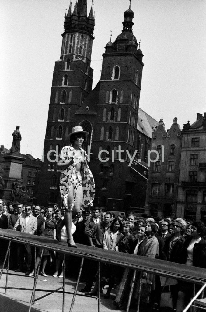 Modelka w jasnej sukience i kapeluszu maszeruje wzdłuż po wybiegu zainstalowanym na placu miejskim, w tle zabytkowe kamienice i wieże kościoła. Dookoła tłum gapiów.