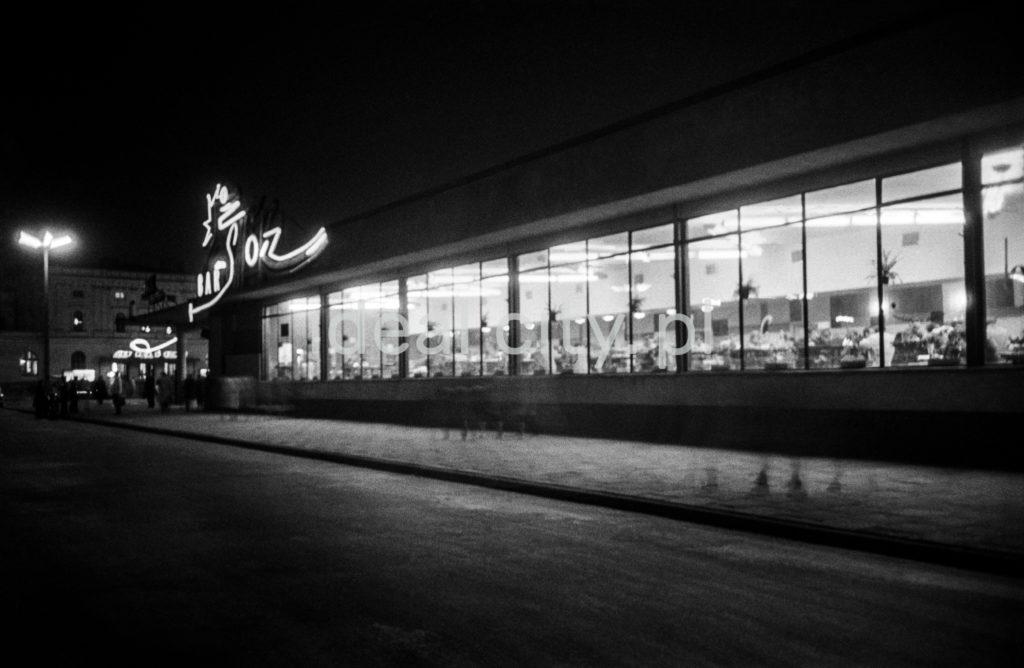 Nocny widok na rozświetlony, modernistyczny pawilon barowy.