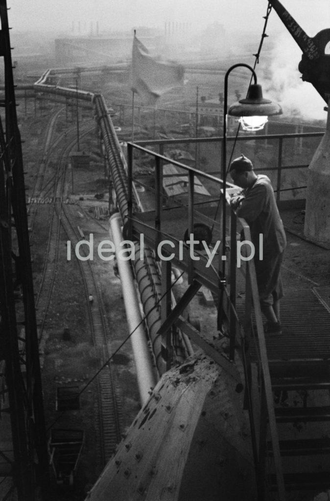 Mężczyzna stoi na pomoście nad halą fabryczną, w tle flaga oraz kominy.