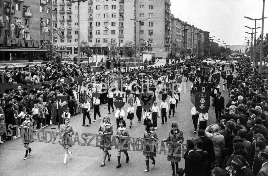 """Pochód młodzieży niesie napis: """"Miasta niegdyś nasze znów są nasze"""", w tle bloki mieszkalne."""