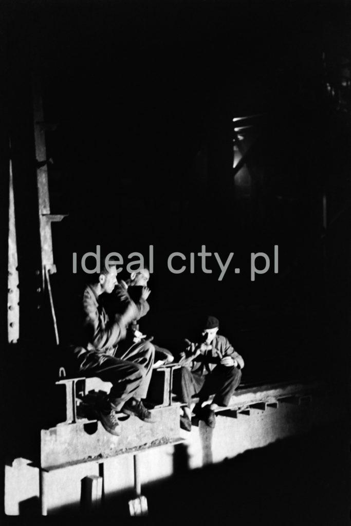 Robotnicy palą papierosy siedząc na przęśle wewnątrz hali fabrycznej.