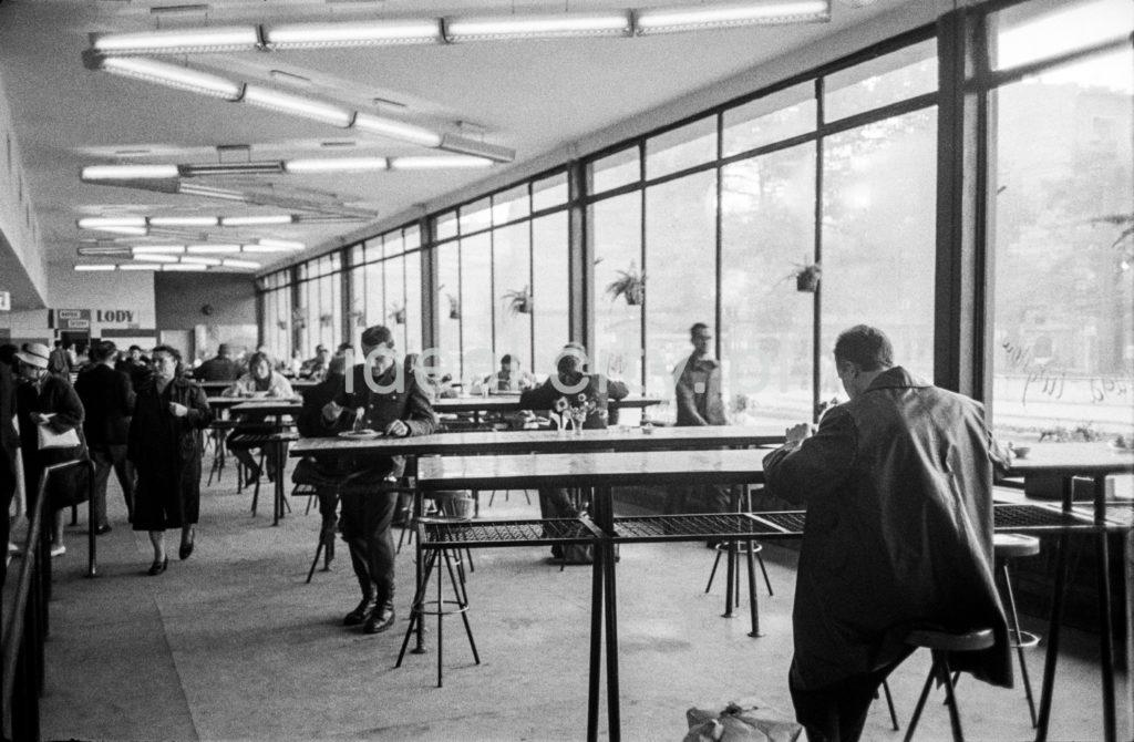 Konsumenci w płaszczach konsumują posiłki we wnętrzu modernistycznego pawilonu barowego.