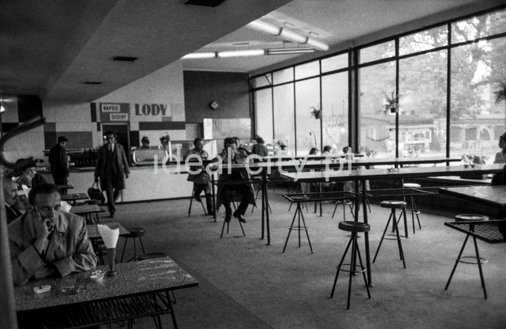 Klienci w ubraniach wierzchnich siedzą przy ławach we wnętrzu modernistycznego pawilonu barowego, na ścianie napis LODY.