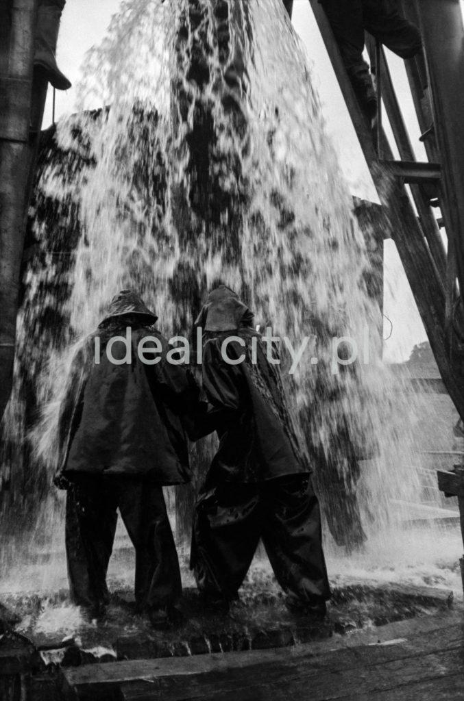Strażacy w sztormiakach dokręcają pochyleni tryskający wodą zawór.