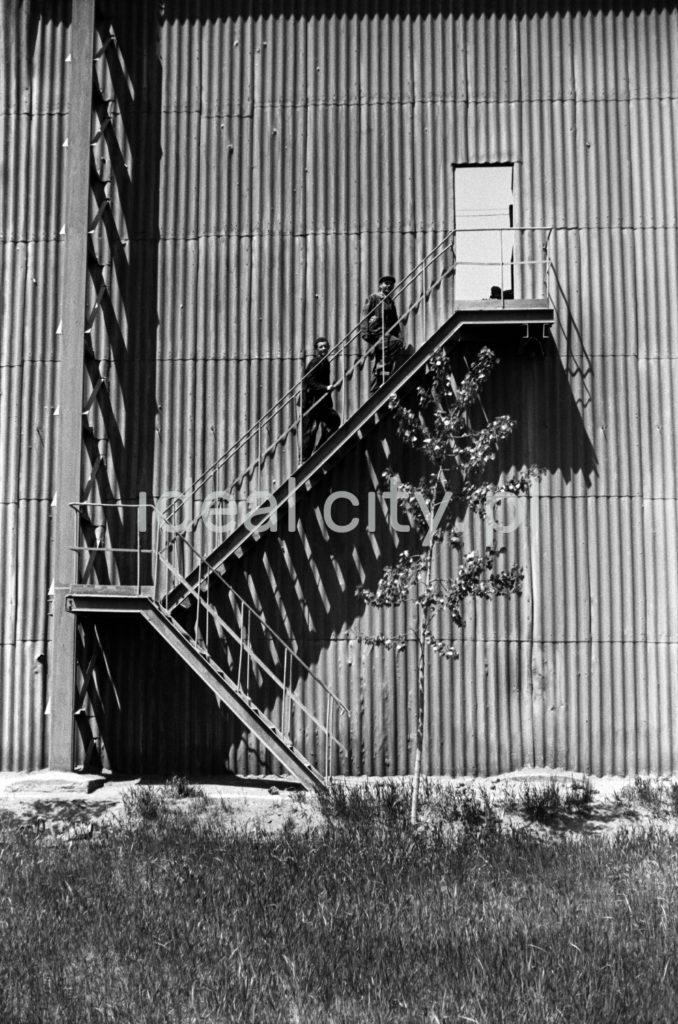 Dwóch mężczyzn wychodzi po zewnętrznych schodach hali fabrycznej.