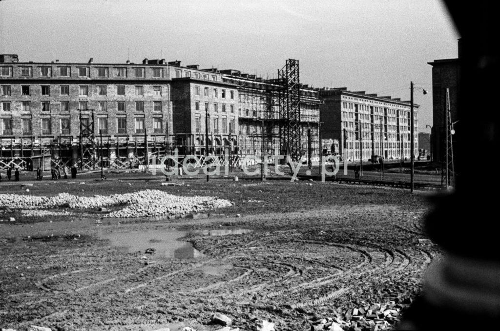 Ujęcie na plac budowy, w tle budynki mieszkalne.