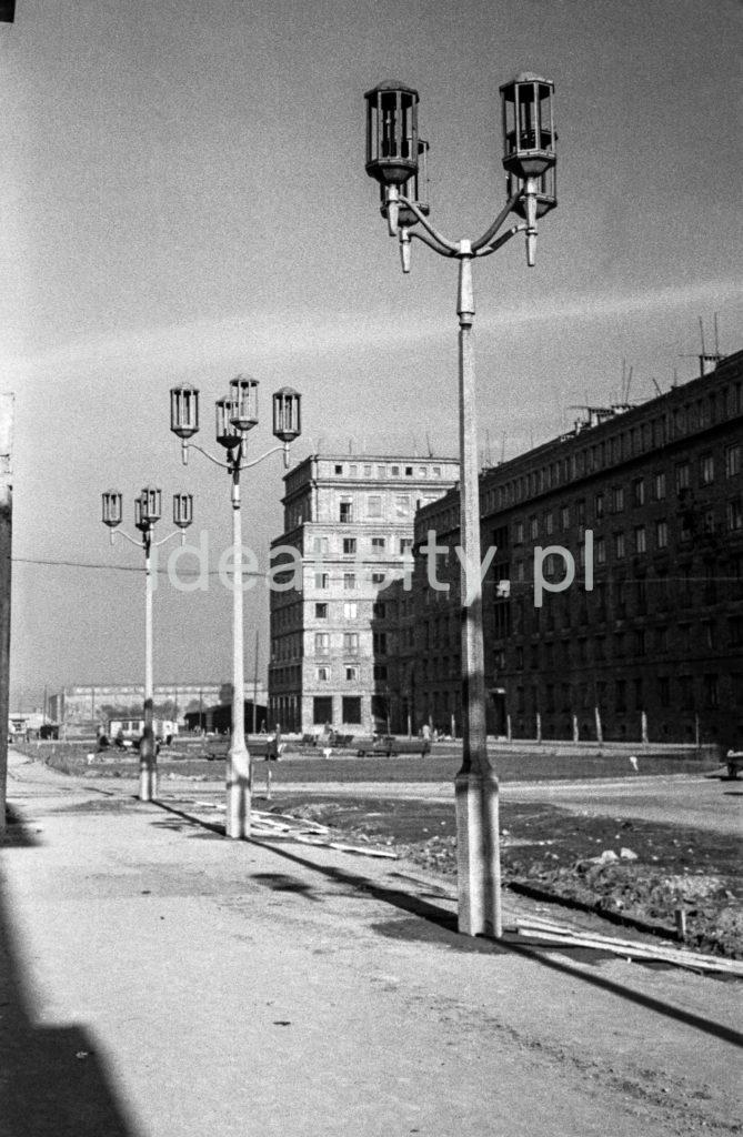 Widok na ciąg monumentalnych latarni, w tle socrealistycznych budynków mieszkalnych.