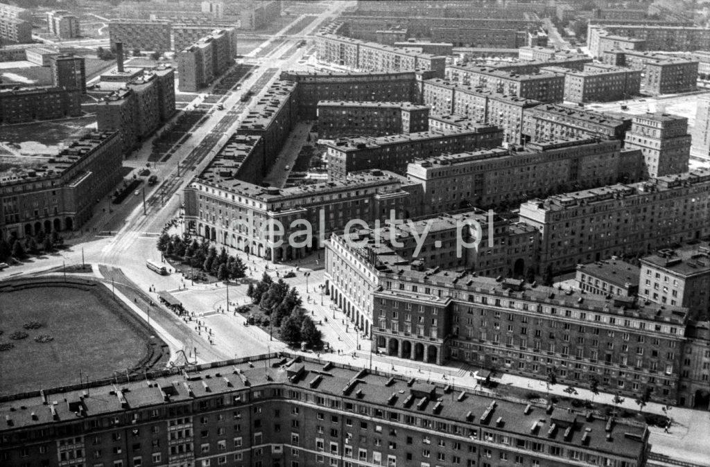 Widok z góry na osadzony centralnie plac miejski z odchodzącymi promieniście ulicami oraz kompleksami budynków.
