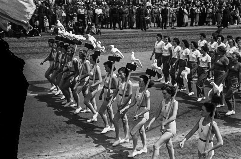 Sportowcy w kostiumach maszerują rzędami w pochodzie