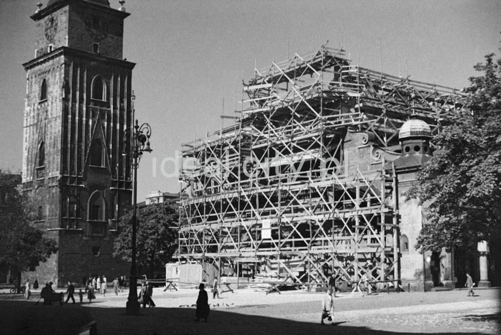 Widok na zakryty rusztowaniami budynek, obok wieźa w stylu gotyckim.