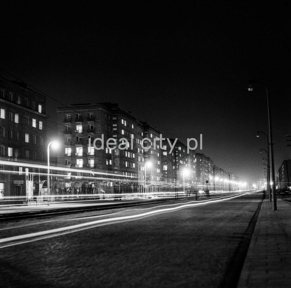 Nocna perspektywa ulicy wraz z budynkami mieszkalnymi widziana z chodnika.