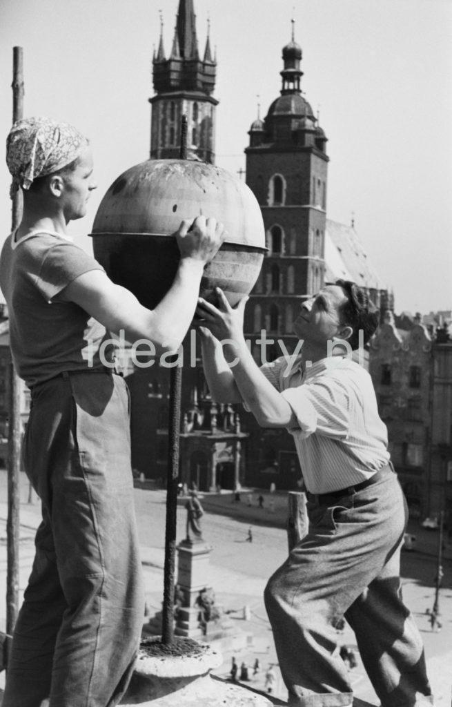 Dwóch mężczyzn montuje blaszaną kopułę na iglicy ulokowanej na dachu budynku. W tle wieże kościoła.