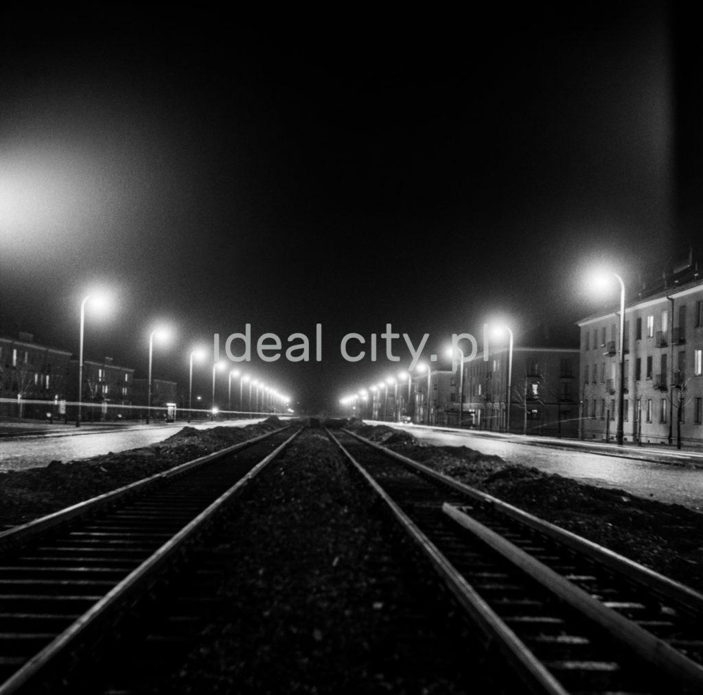 Nocna perspektywa ulicy fotografowana ze środka torowiska tramwajowego