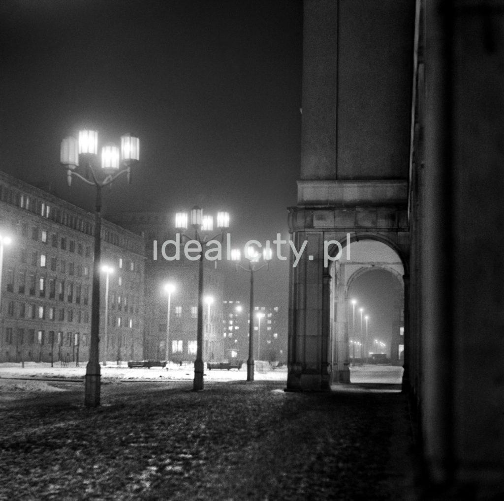 Nocna perspektywa ulicy, widoczne monumentalne arkady oraz latarnie.