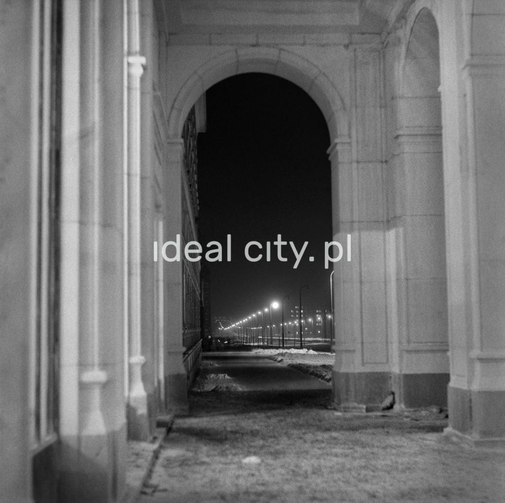 Nocna perspektywa ulicy widzian spod monumentalnych arkad.