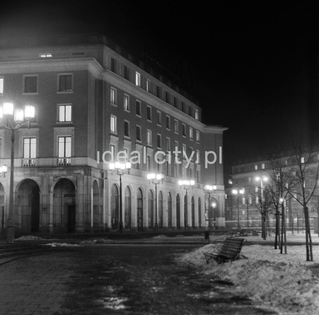 Nocne ujęcie na mokry chodnik przed monumentalnym budynkiem mieszkalnym, oświetlony latarniami.