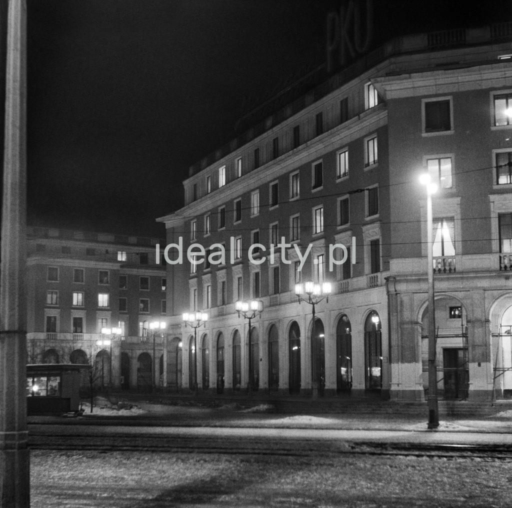 Nocne ujęcie na zmoczony deszczem chodnik przed monumentalnym budynkiem mieszkalnym, oświetlony latarniami.