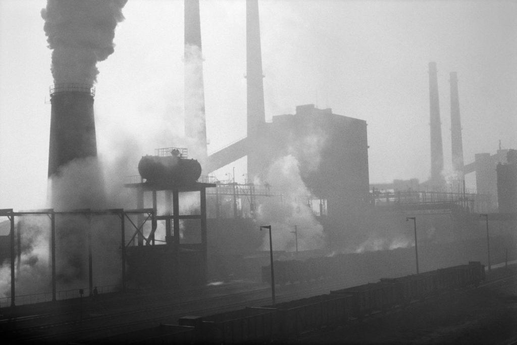 Widok na dymiące kominy fabryki.