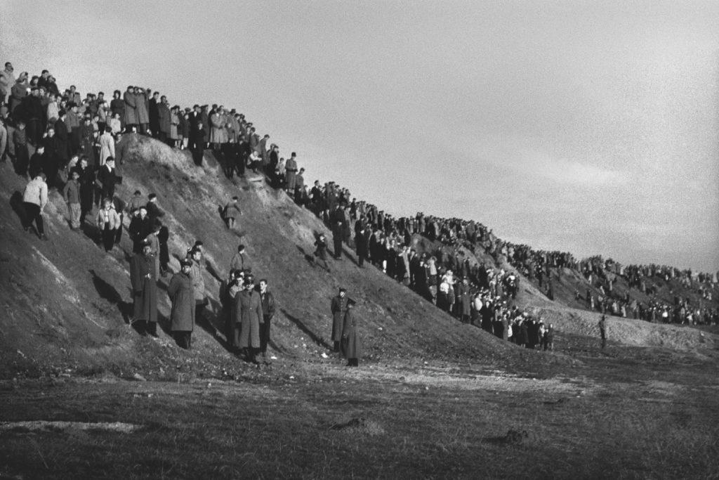 Tłumy ludzi na zboczu ciągnącej się wzdłuż porośniętego trawą przepłaszczenia.