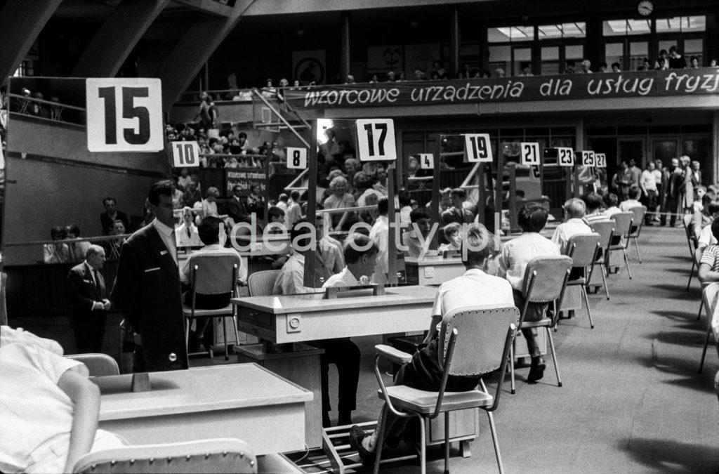 Symetryczne ujęcie przez dwa rzędy stolików ustawionych na płycie dużej hali sportowej, przy każdym ze stolików siedzi młody człowiek.