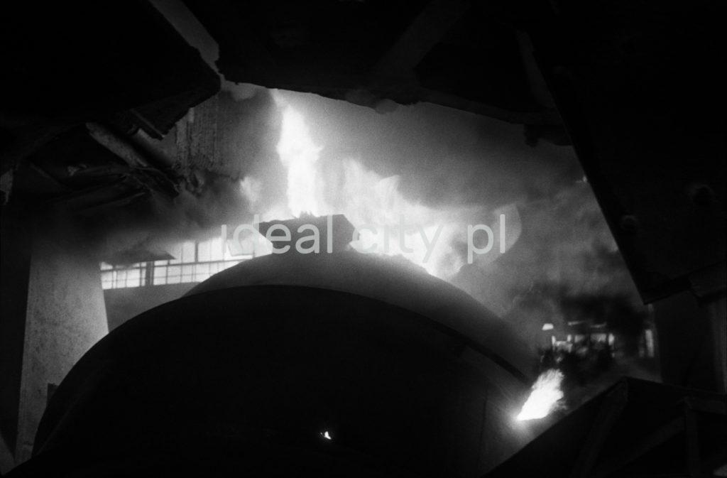 Widok z dołu na potężny piec, z góry którego bucha ogień.