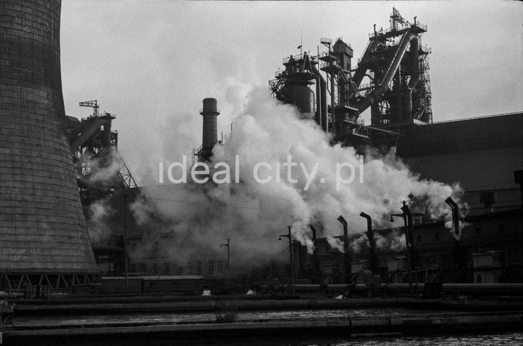 Ujęcie na ginące w dymach obiekty i kominy farbyczne w gęstej zabudowie.