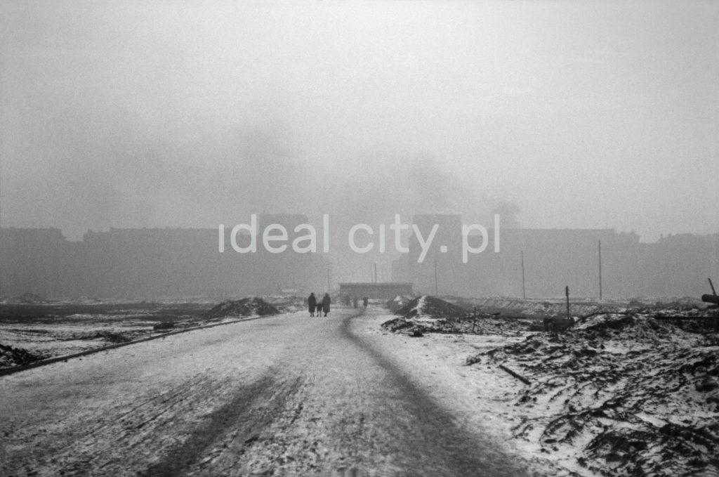 Zimowy widok przez pokrytą śniegiem drogę i zryte pola w stronę budynków mieszkalnych.