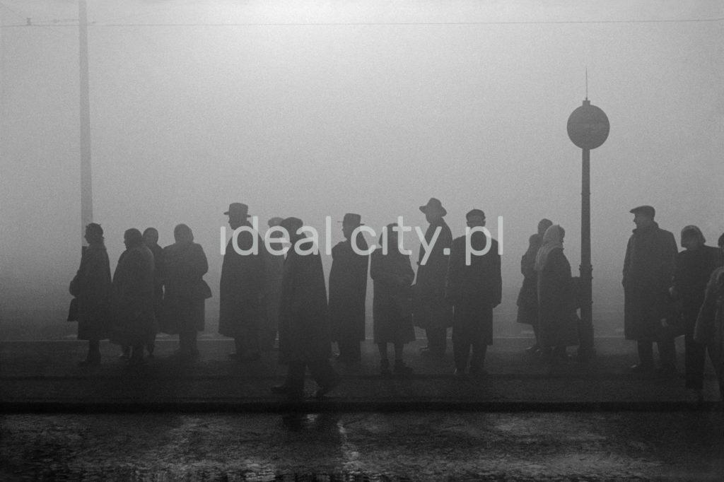 Sylwetki ludzi w płaszczach i kapeluszach stojących we mgle mna przystanku tramwajowym.