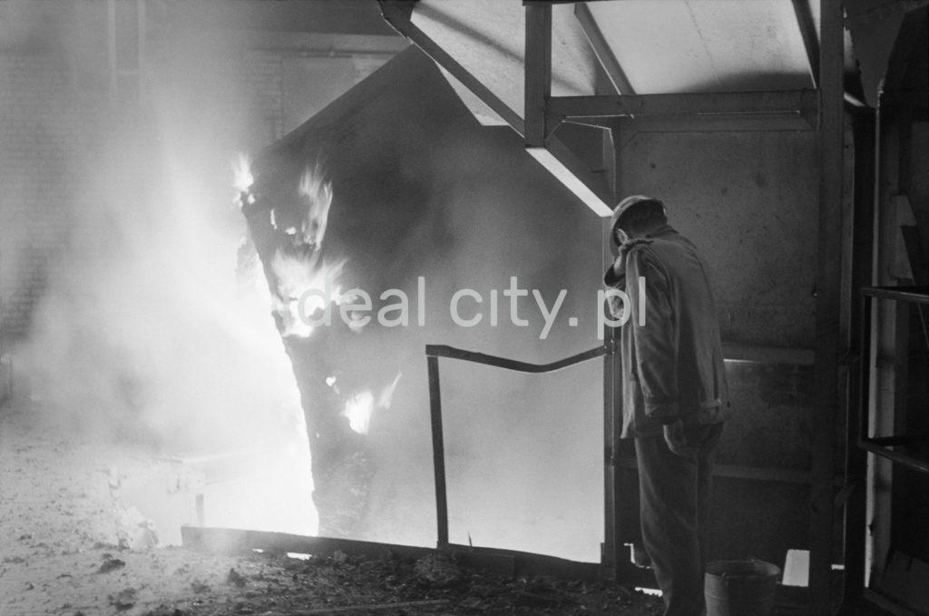 Mężczyzna w kasku stojąc na metalowej zwyżce nachyla się nad ziejącą ogniem instalacją.