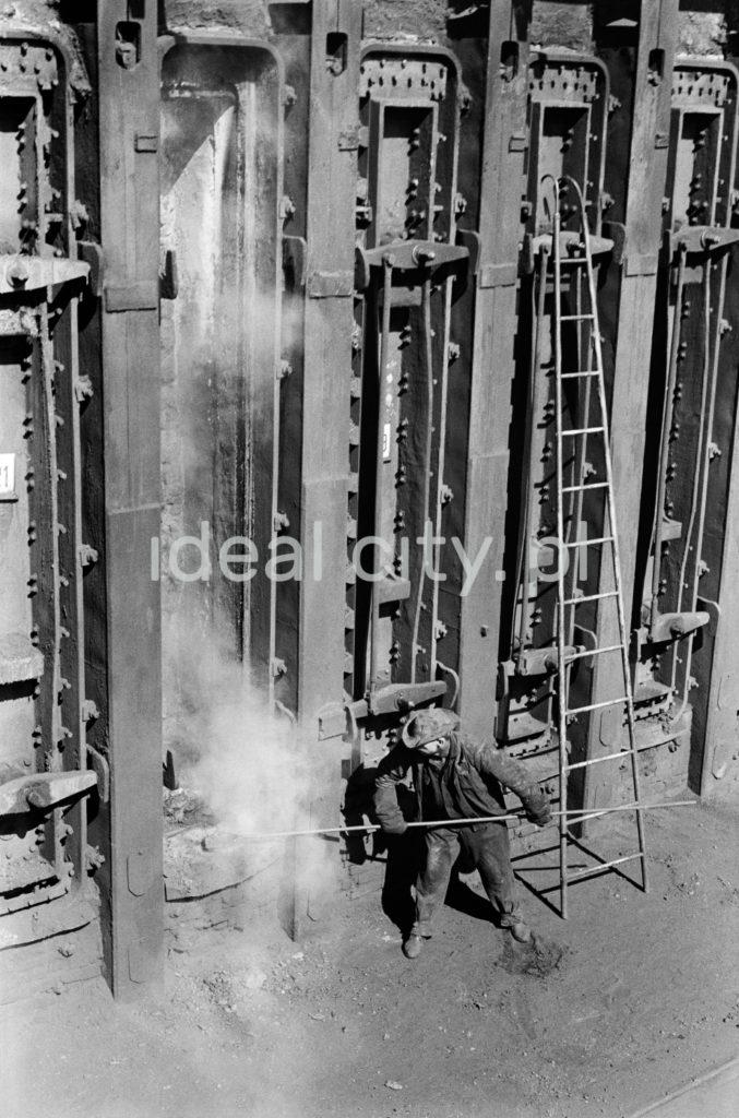 Pracownik w stroju roboczym wprowadza długi pręt do baterii koksowniczej.