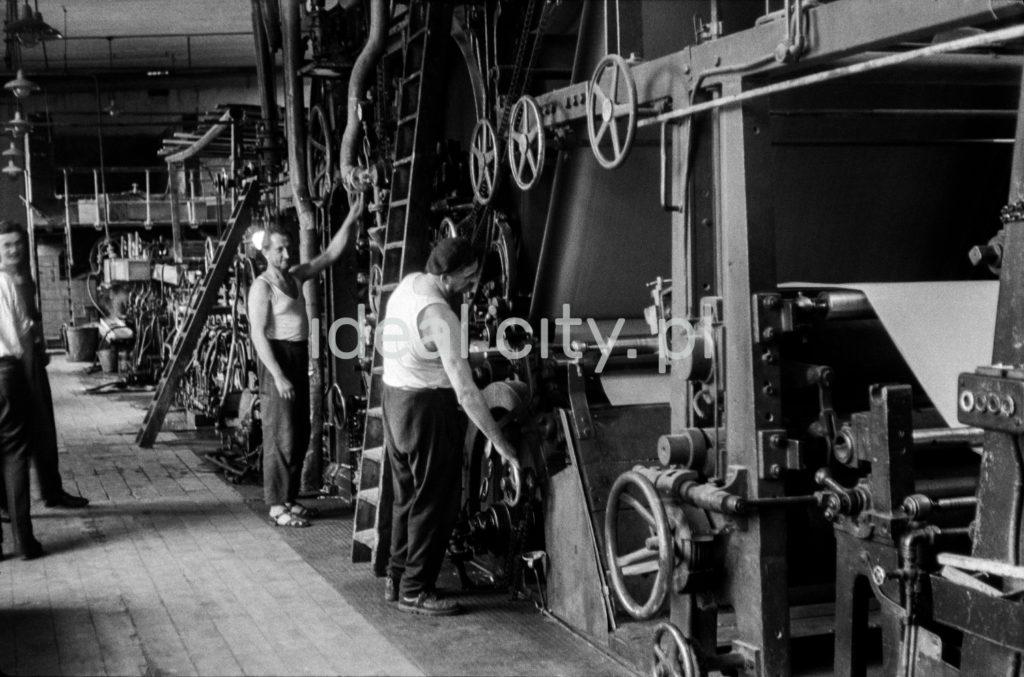 Mężczyźni w podkoszulkach na ramionach regulują ciąg maszyn.