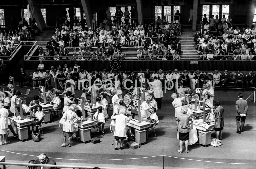 A shot from a height on the tables with participants set up in the center of the hall, and the audience in the background.