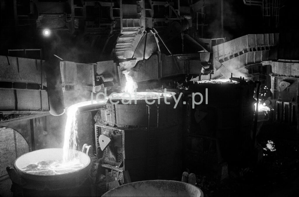 In a huge dark hall, molten iron is poured from one open vat to another.